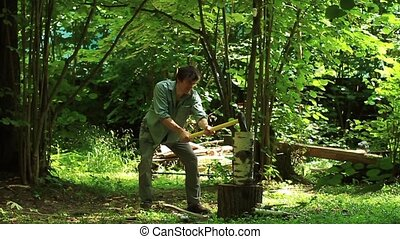 Man with an ax chops wood for heating HD