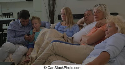 Family on the sofa watching TV together - Big family...