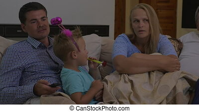Parents and son watching TV at home
