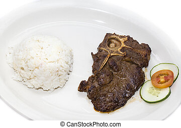 T Bone steak with rice and sauce on a white plate in a...