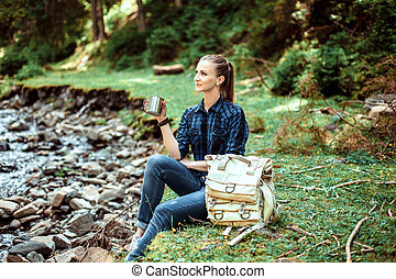 Young tourist girl sitting on the shore of a mountain river...