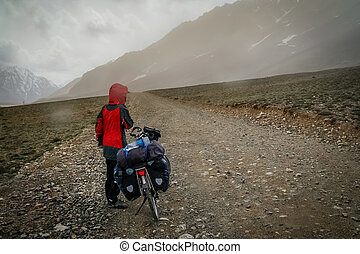 Up the Shandur Pass - Cyclist dressing up in waterproof and...