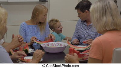 Eating watermelon in the dining room - Family enjoying ripe...