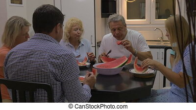 Big family eating watermelon in the kitchen