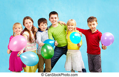Holiday - Portrait of smiling children holding balloons and...