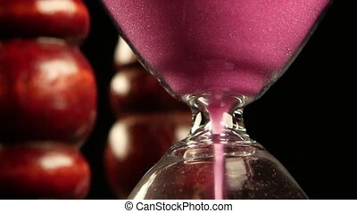 Hourglass in wooden stand. Pink sand. Close up - Sand in an...