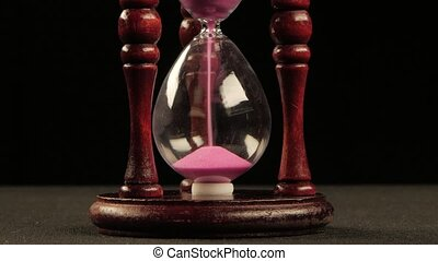 Hourglass in wooden stand. Pink sand. Black. Close up - Sand...