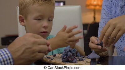 Child and parents modeling with playdough - Little boy and...