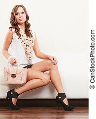 Fashionable girl with handbag sitting on sofa