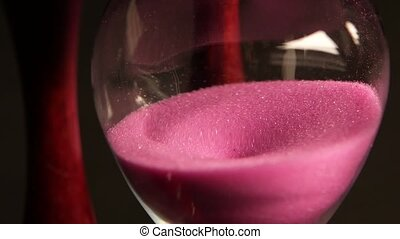 Hourglass is ticking. Pink sand. Black. Close up - Pink sand...