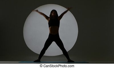 Woman makes tilting sideways. Stretching. Back light. Silhouette.