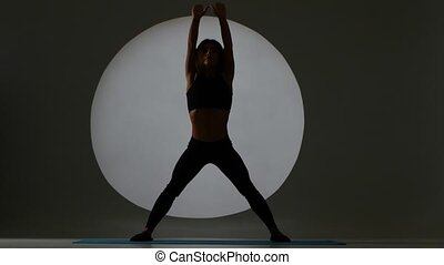 Stretching. Woman doing a forward bend. Back light. Silhouette