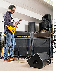 Playing electric guitar in a jam room