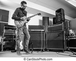 Practicing his electric guitar in a jam room
