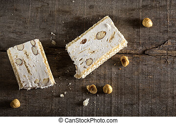 Torrone or nougat with nuts on wood background