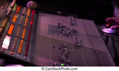 Male hands using a sound digital mixer at a concert