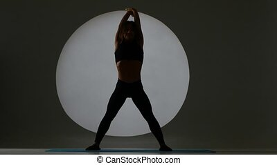 Woman bends the body on the fitness. Back light. Silhouette...