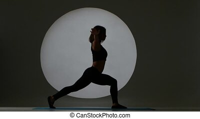 Girl doing stretching with one bent-knee leg. Back light. Silhouette