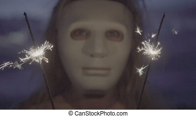 Woman in white mask with sparklers - Closeup of scarry...