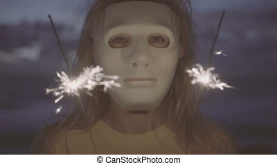 Woman in white mask with sparklers. - Closeup of scarry...