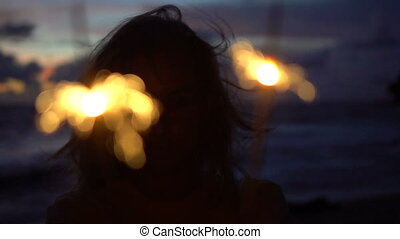 Woman with sparklers on the beach - Closeup of happy woman...