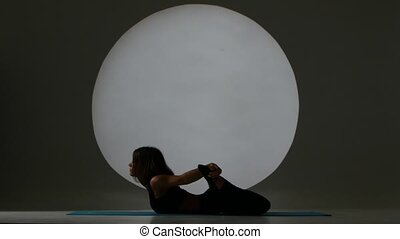 Girl in pose on the stomach does stretch. Back light. Silhouette