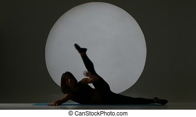 Woman doing stretching exercises. Back light. Silhouette -...