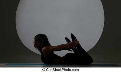 Woman in pose on the stomach does stretch. Back light. Silhouette