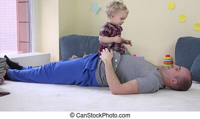 Lovely baby girl sits on dad stomach and embrace loving father.