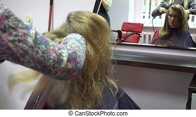 stylist drying hair with round brush. Girl before mirror. 4K...