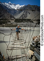 Crossing The Bridge - Woman traveller crossing the unstable...