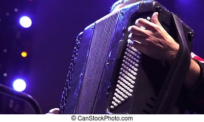 Musician hand playing accordion closeup in stage lights...