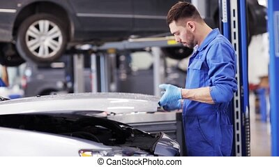 mechanic man with wrench repairing car at workshop - car...