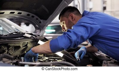mechanic man with wrench repairing car at workshop 4 - car...