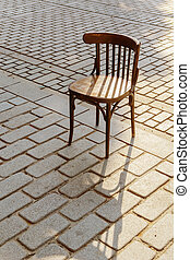 Old Viennese chair on the cobbles in the setting sun - Old...