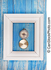 Old Compass in Photo frame on blue background