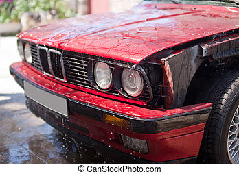 Front part of red car without wing with water drops on car wash