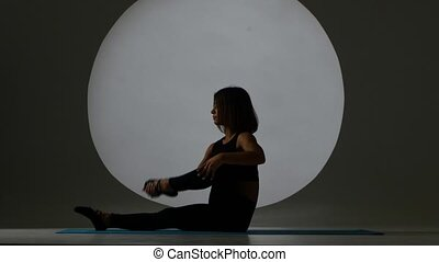 Woman sitting on yoga mat and is stretching legs. Back...