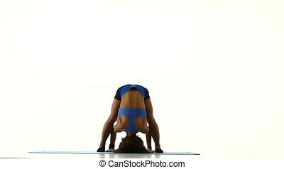 Gymnast stands on her head and changes the pose of legs. White