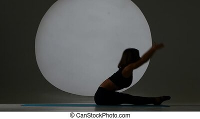Athlete doing the splits lying on back Back light Silhouette...