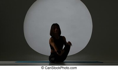 Gymnast sitting on the mat gets a leg behind her head. Back light. Silhouette
