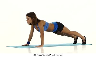 Gymnast performs exercises on push-ups. White