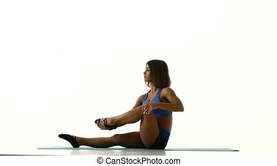 Athlete sitting on yoga mat and is stretching legs. White -...
