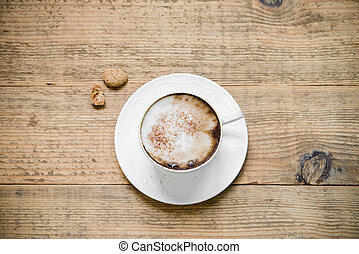 Cup of cappuccino with biscotti on woode table - Cup of...