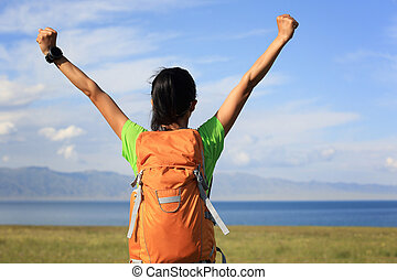 cheering young woman hiker open arms to beautiful landscape