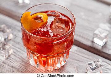 Glass with dark orange drink.