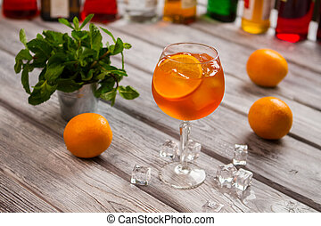 Wineglass with orange cocktail. Mint in small bucket. Aperol...