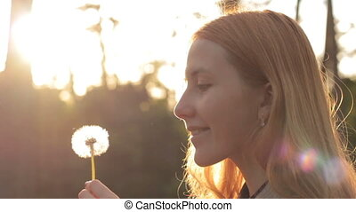 Side view of blonde girl blowing on dandelion
