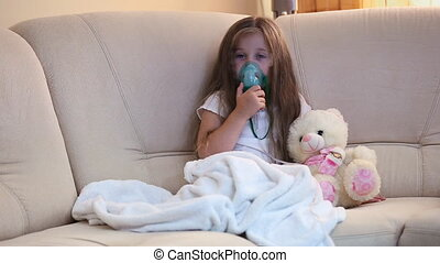 Little girl making inhalation sitting on sofas