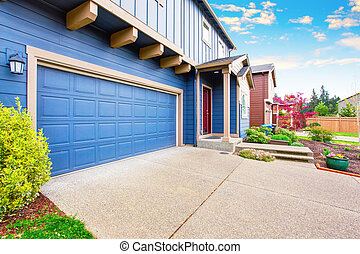 Blue house exterior. View of garage and porch with red...